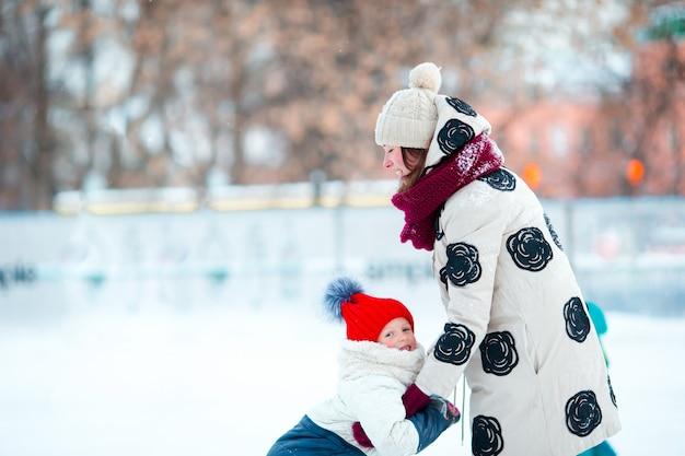 Menina adorável com a mãe patinar na pista de gelo com a mãe
