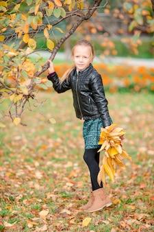Menina adorável com buquê de folhas amarelas em queda na scooter