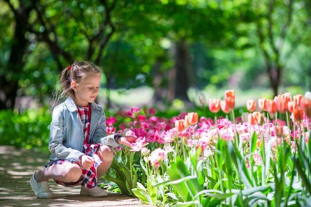 Menina adorável com flores no jardim de tulipas