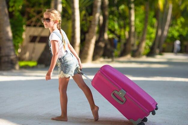 Menina adorável com grande bagagem durante as férias de verão