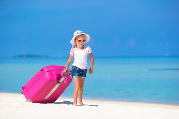 Menina adorável com mala grande na praia tropical branca
