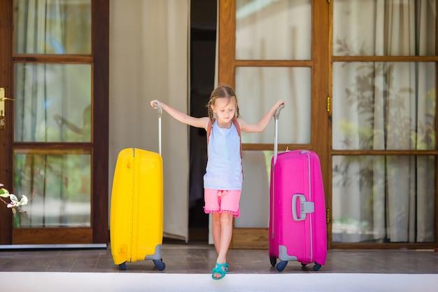Menina adorável com malas prontas para viajar