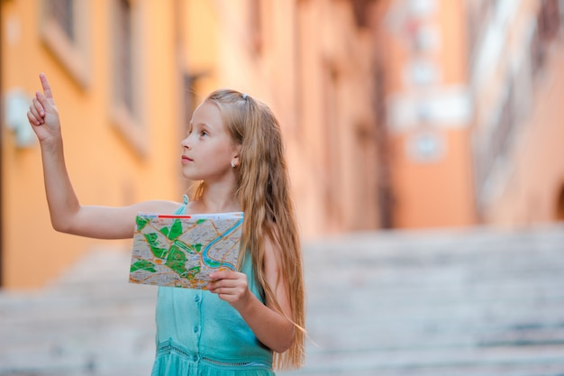 Menina adorável com o mapa turístico nas ruas romanas em itália. a criança feliz do toodler aprecia o feriado italiano das férias em europa.