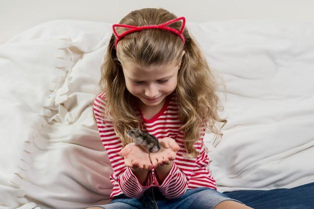 Menina adorável com seu pequeno hamster de estimação