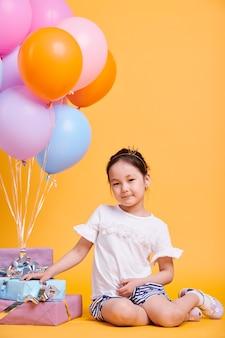 Menina adorável com uma pequena coroa na cabeça sentada isolada perto de uma pilha de presentes de aniversário e um monte de balões