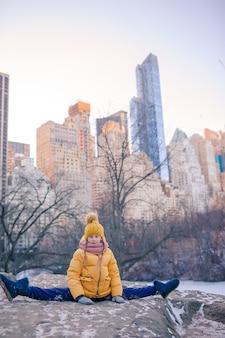 Menina adorável com vista para a pista de gelo no central park, em manhattan, na cidade de nova york