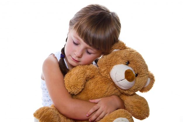 Menina adorável criança abraçando um ursinho de pelúcia