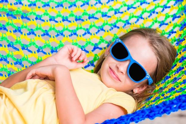 Menina adorável de férias tropicais relaxantes na rede