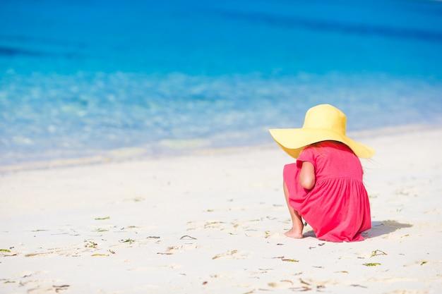 Menina adorável desenho na areia branca na praia