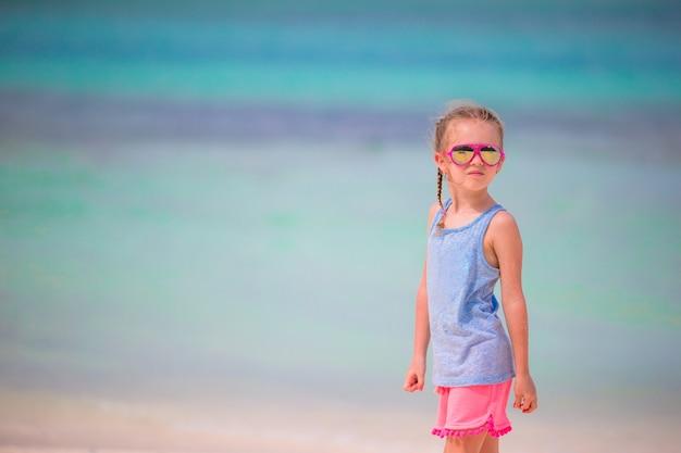 Menina adorável durante as férias de praia se divertindo