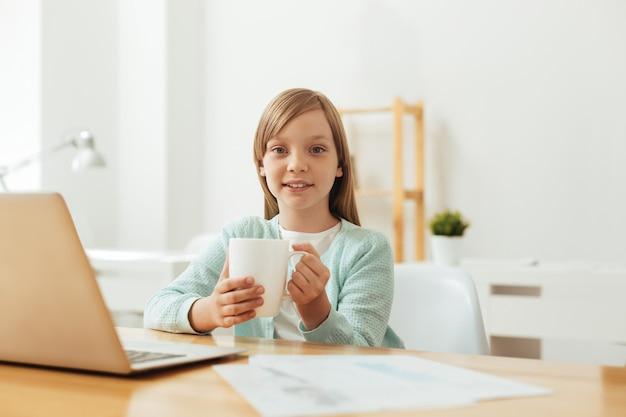 Menina adorável e encantadora comprometida ficando quente e aconchegante enquanto lia um artigo e trabalhava em sua casa