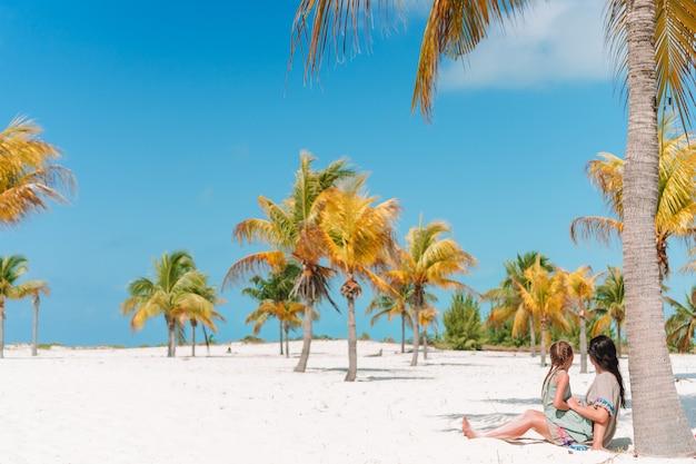 Menina adorável e jovem mãe na praia tropical