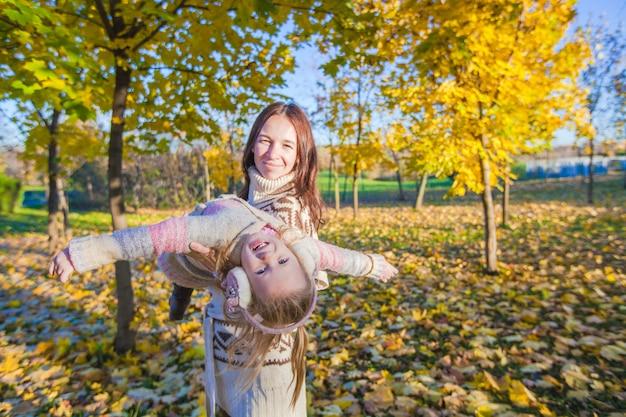 Menina adorável e jovem mãe se divertindo no parque outono em dia ensolarado