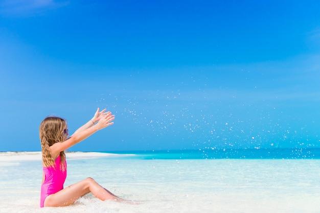 Menina adorável em águas rasas na praia