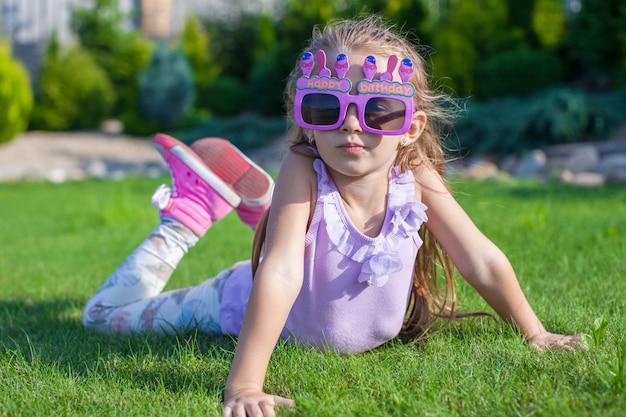 Menina adorável em copos de feliz aniversário sorrindo ao ar livre