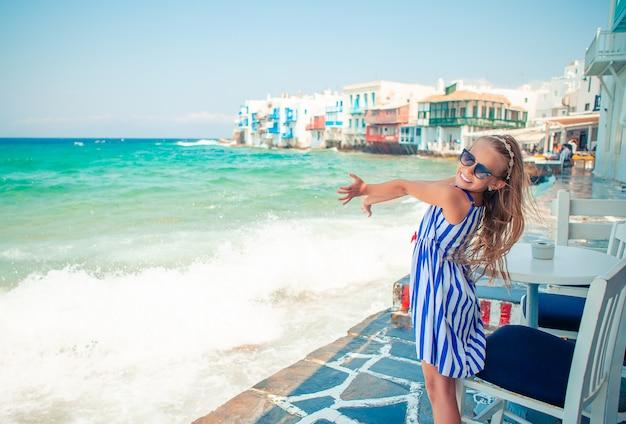 Menina adorável em little venice a área turística mais popular na ilha de mykonos, grécia.