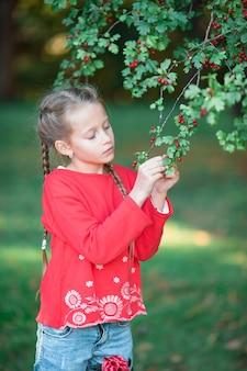 Menina adorável em macieira florescendo jardim na primavera