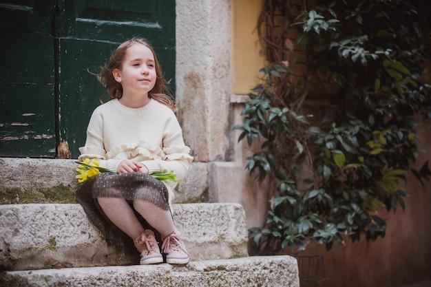 Menina adorável em roupas da moda senta-se perto da porta velha na cidade velha em dia ensolarado de primavera