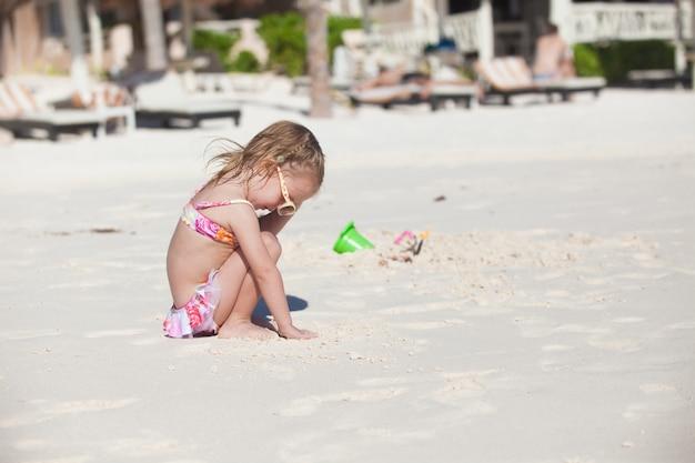 Menina adorável em traje de banho na praia tropical das caraíbas