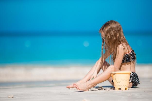 Menina adorável em traje de banho na praia tropical