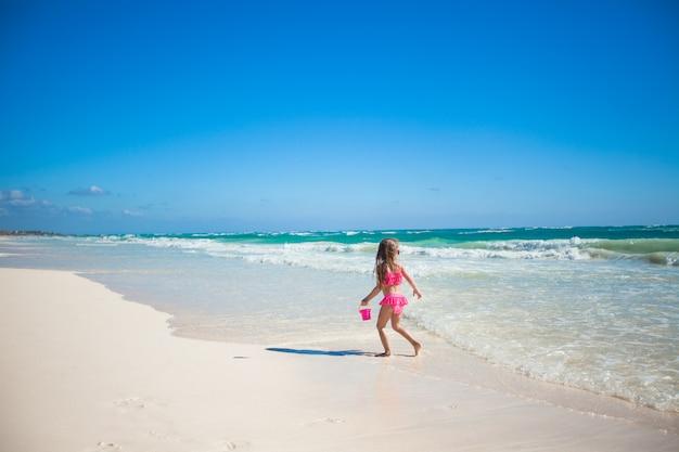 Menina adorável em traje de banho se divertindo na praia tropical das caraíbas