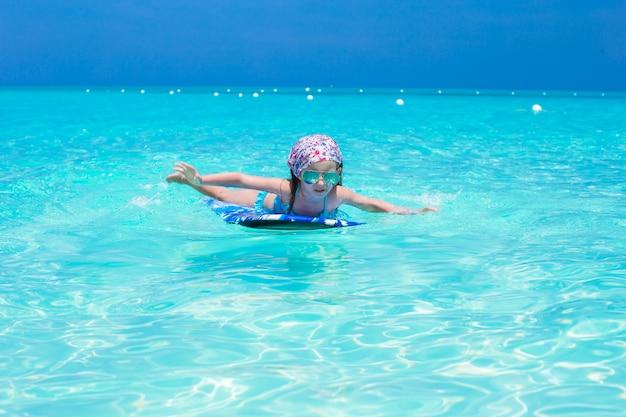 Menina adorável em uma prancha de surf no mar azul-turquesa