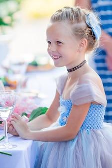 Menina adorável em vestido incrível em uma cerimônia de casamento ao ar livre