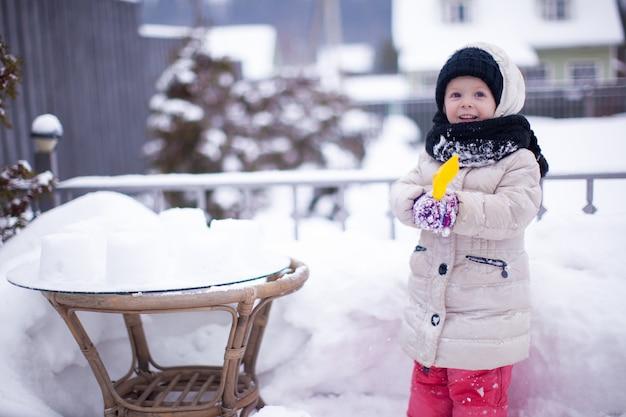 Menina adorável engraçado se divertindo e jogando no quintal no dia ensolarado de inverno