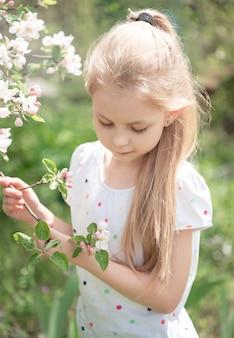 Menina adorável entre a árvore em flor no jardim de maçãs