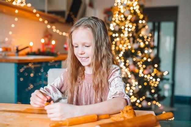 Menina adorável fazendo biscoitos de gengibre de natal