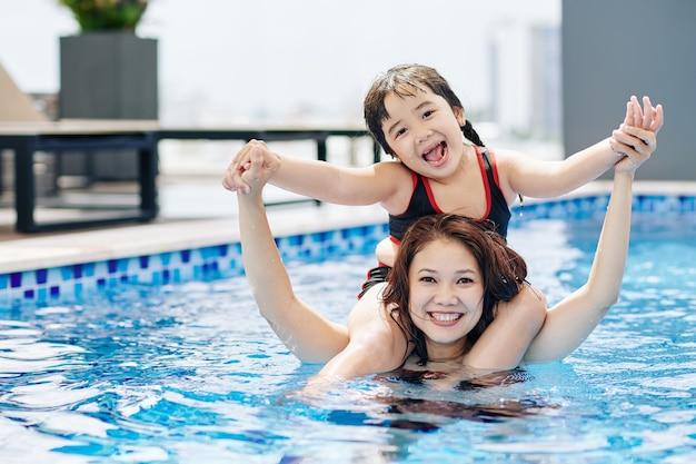 Menina adorável, feliz e animada sentada nos ombros da mãe quando elas estão brincando na piscina juntas