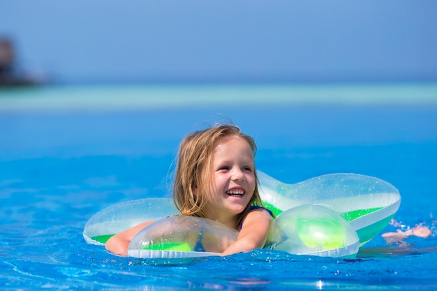 Menina adorável feliz na piscina ao ar livre