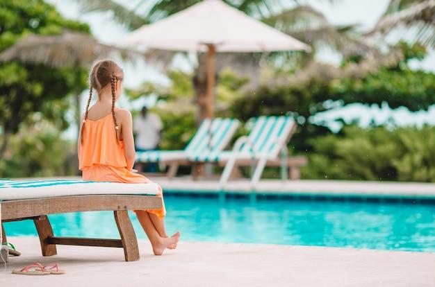 Menina adorável feliz pequena na piscina ao ar livre