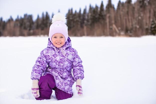 Menina adorável feliz se divertindo na neve no dia ensolarado de inverno