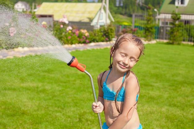 Menina adorável feliz sorrindo e derramando água de uma mangueira