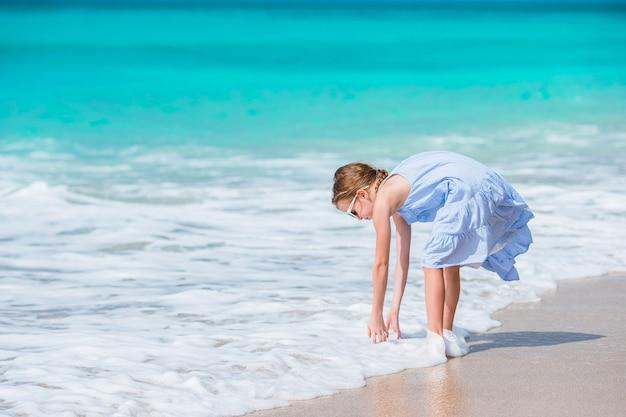 Menina adorável na água pouco profunda. garoto bonito, lavar as mãos na onda