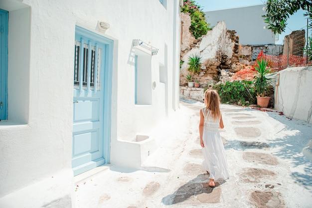 Menina adorável na antiga rua da aldeia tradicional grega típica