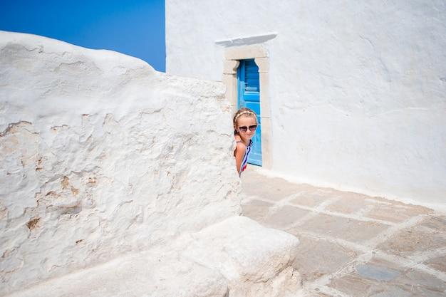 Menina adorável na antiga rua da típica aldeia tradicional grega