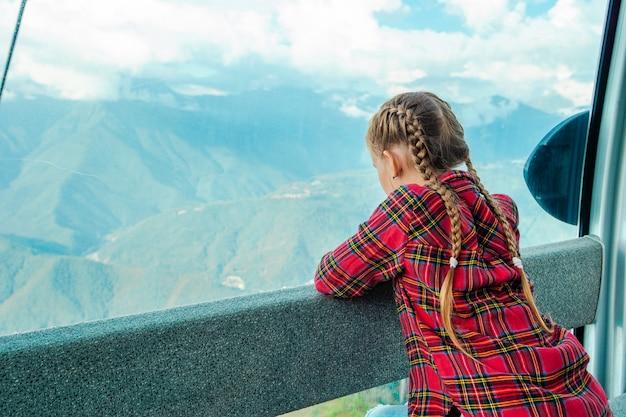 Menina adorável na cabine no teleférico nas montanhas