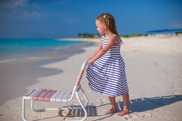Menina adorável na cadeira de praia durante as férias do caribe