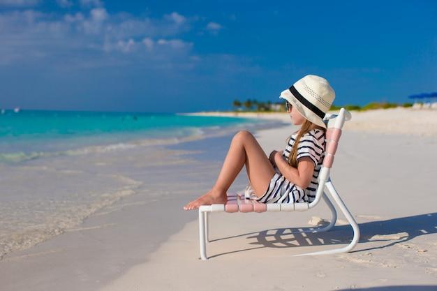Menina adorável na cadeira de praia durante férias nas caraíbas