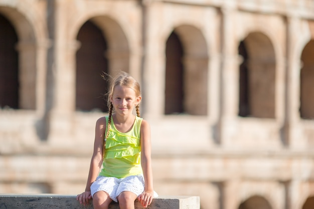 Menina adorável na frente do colosseum em roma, itália. garoto em férias italianas