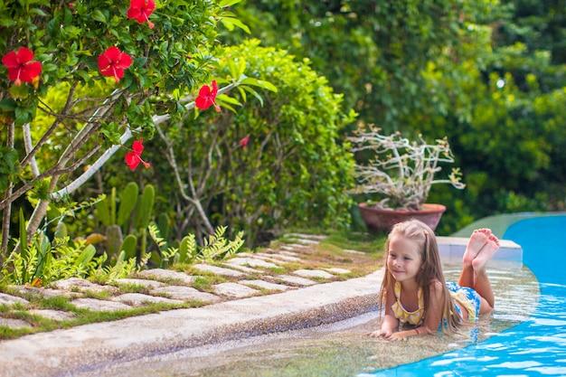 Menina adorável na piscina olha para a câmera