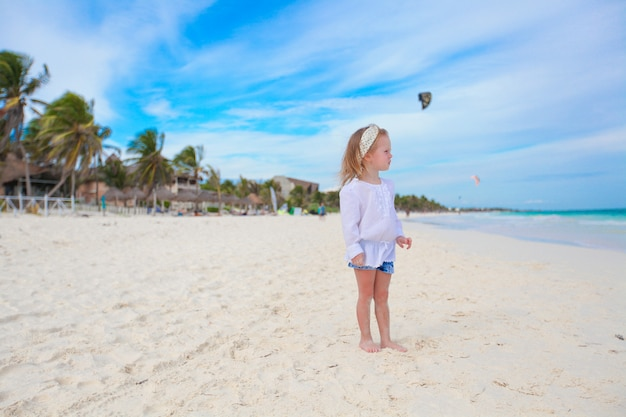 Menina adorável na praia branca das caraíbas no dia ensolarado
