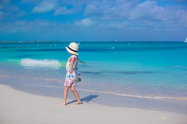 Menina adorável na praia branca durante as férias de verão