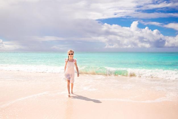 Menina adorável na praia se divertindo muito em águas rasas