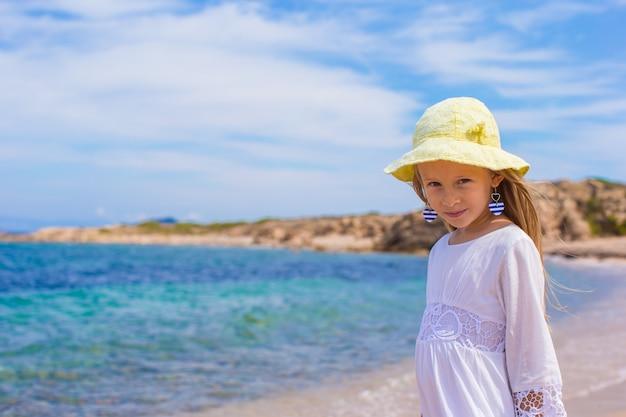 Menina adorável na praia tropical durante as férias