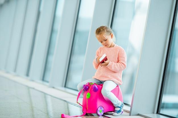 Menina adorável no aeroporto com sua bagagem à espera de embarque