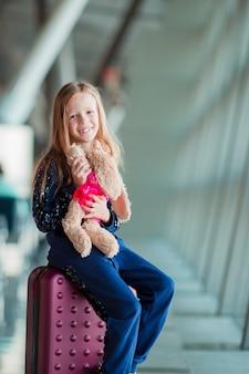 Menina adorável no aeroporto perto da grande janela interior
