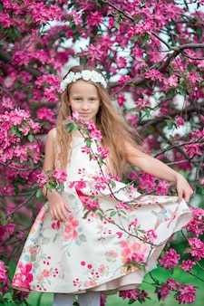 Menina adorável no belo jardim de maçã florescendo ao ar livre